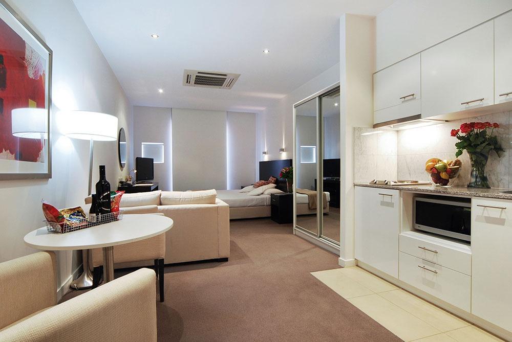 квартира студия, совмещенные комнаты, теплый оттенок стен, белая кухня