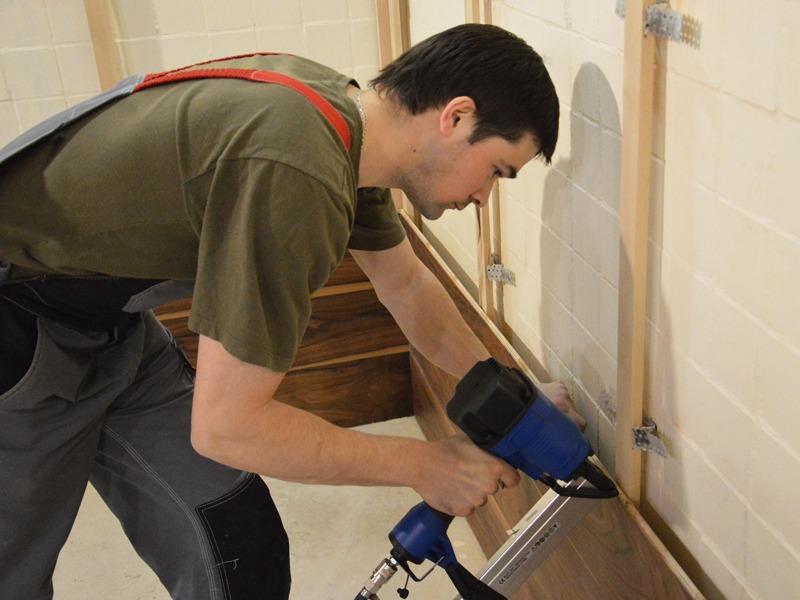 Установка деревянного каркаса, отделка стены деревом, мастер делает ремонт